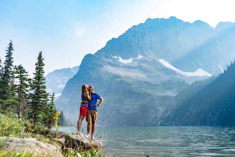 Couple standing by lake against mountain
