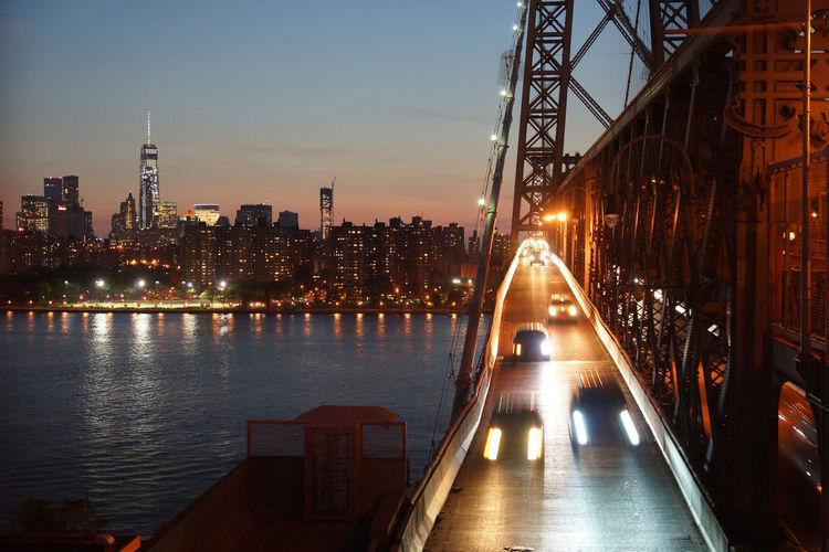 Illuminated manhattan against sky seen from williamsburg bridge over east river