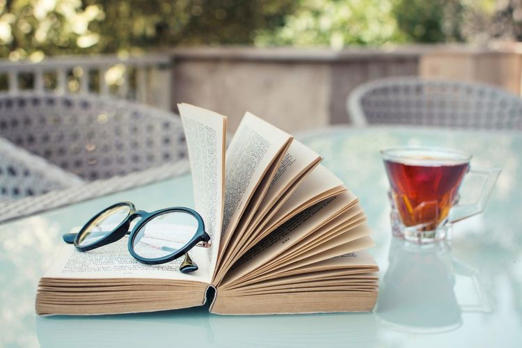Close-up of eyeglasses and book with drink on table