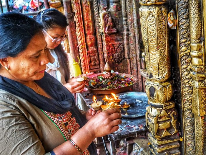 Women devotees offer butter lamps at Buddhist shrine Kathmandu Nepal Two Women Religious  Brass Decoration Prayer Religion And Tradition Ritual Worship Buddhism Kathmandu, Nepal Butter Lamps Belief Real People Religion Lifestyles Holding Spirituality Women