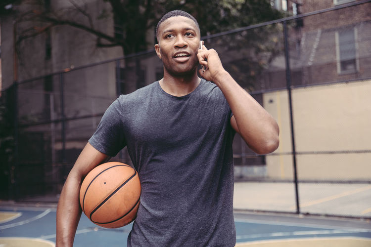 Young man talking on mobile phone while standing in basketball court