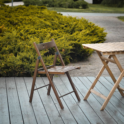 Empty chairs and table on grass