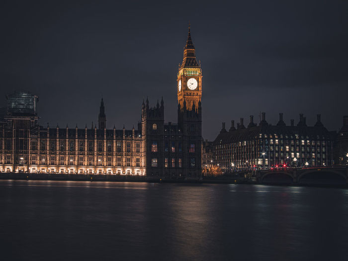 Big ben by river against sky in city at night