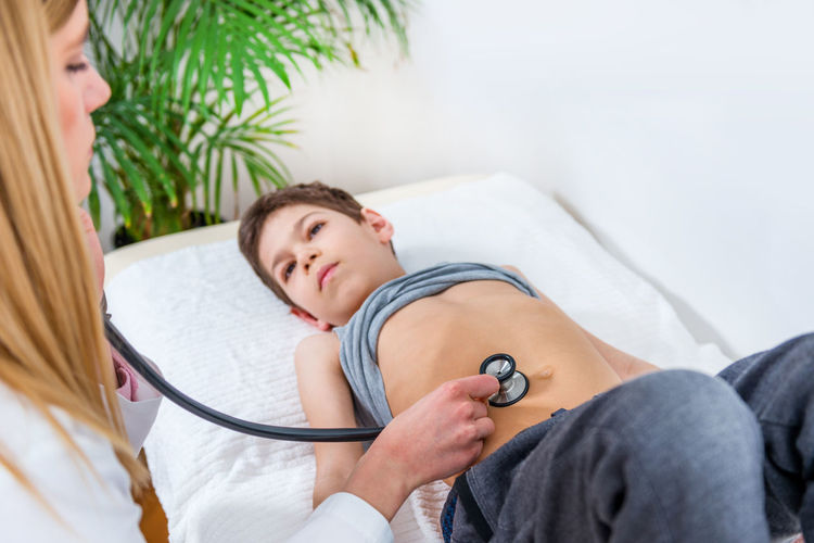 Pediatrician Examining Boy's Abdomen Doctor  Pediatrician Medical Child Boy School Boy Human Abdomen Abdomen Examining Touching Stomach Laying Checking Check Up Medicine Hospital Clinic Patient Health Kid Talking Stetoscope Healthcare Care Childhood Female People Exam Professional Examination White Healthy Office Sick Adult Illness Diagnostic Lifestyle Woman Occupation Pediatric Specialist Examine Diagnosis Expertise
