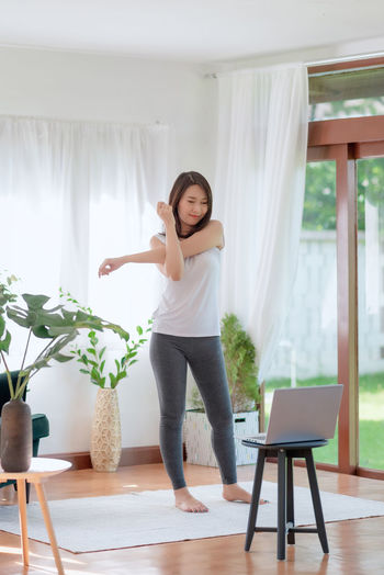 Woman standing on table at home
