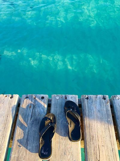 High Angle View Of Slippers On Pier Over Sea