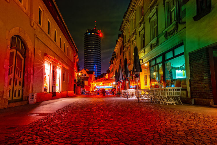 Illuminated street amidst buildings at night