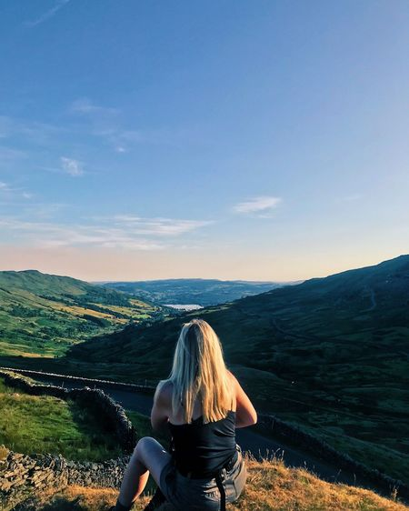 Rear view of woman looking at landscape against sky
