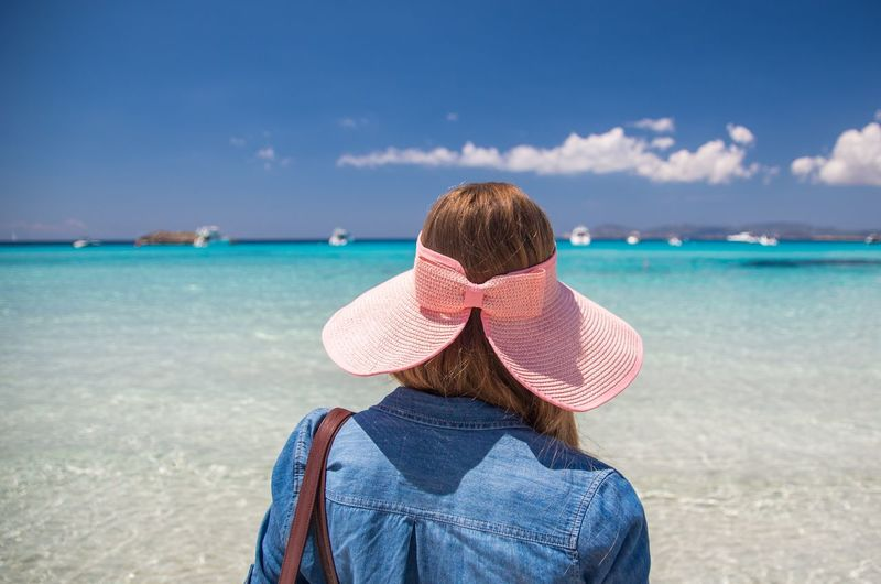 Rear view of woman with pink hat standing on beach