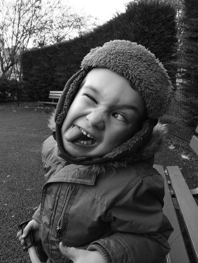 Playful boy making face at park