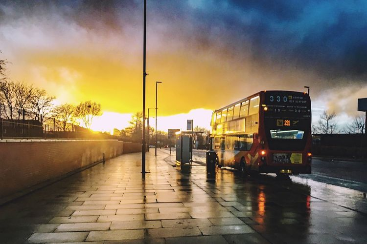 SUN SETS IN THE EAST Sky Transportation Mode Of Transportation Sunset Cloud - Sky Land Vehicle City Men Wet Nature Group Of People Architecture Real People Outdoors Lifestyles Public Transportation Footpath Road Built Structure Street The Street Photographer - 2018 EyeEm Awards Streetwise Photography