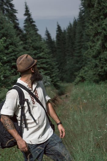 Male Hiker With Backpack Standing On Grassy Field In Forest