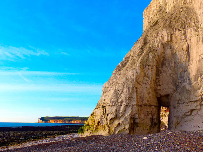 Rock formations by sea against blue sky