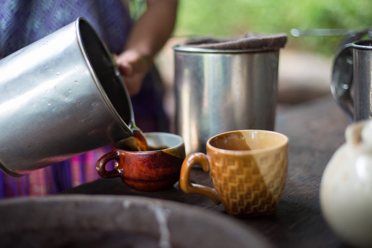 Cropped image of person pouring black tea in cup on table