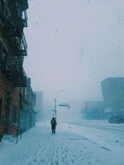 Rear view of person walking on sidewalk in city during blizzard