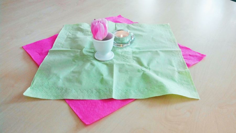 Pink tulip in eggcup on tissue paper over table