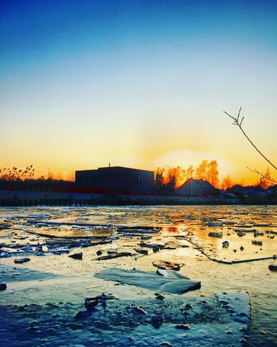 Broken pieces of ice on a frozen river or canal at sunrise or sunset in wintertime Sky Sunset Water Nature Beauty In Nature Scenics - Nature Tranquility Tranquil Scene No People Orange Color Silhouette Copy Space Winter Clear Sky Outdoors Reflection Snow Waterfront Sunlight
