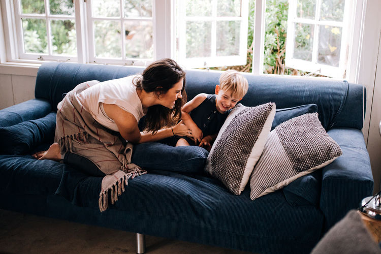 Mother playing with cute son while sitting on sofa at home