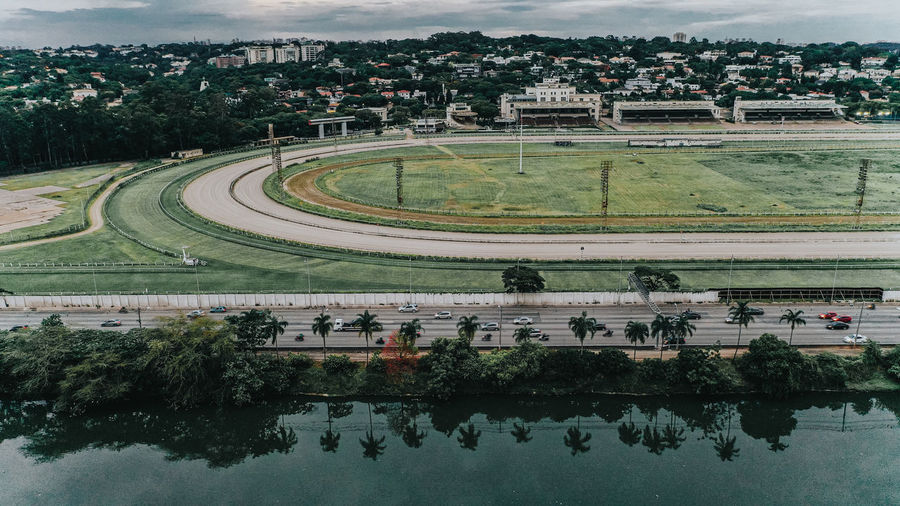 Aerial view of sports track by canal against sky