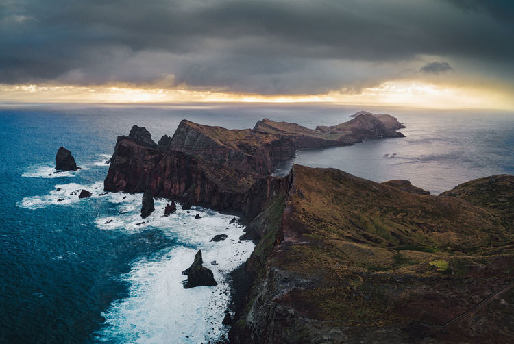 Rain and sunrise above the rugged coastline.