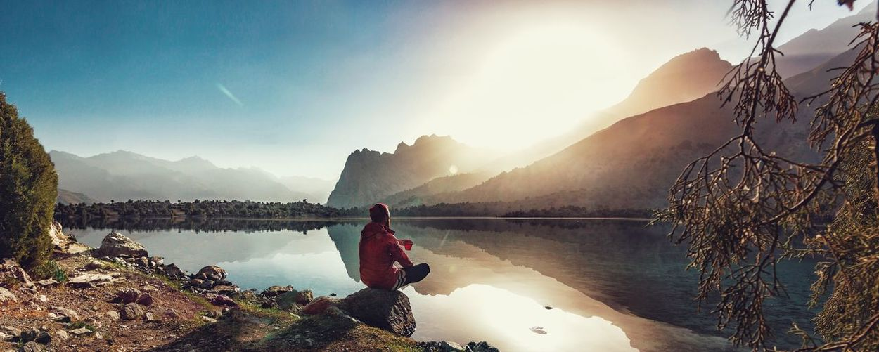 Man looking at view while sitting on rock by lake against mountains and sky during sunset