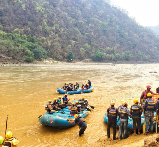 People river rafting by mountain