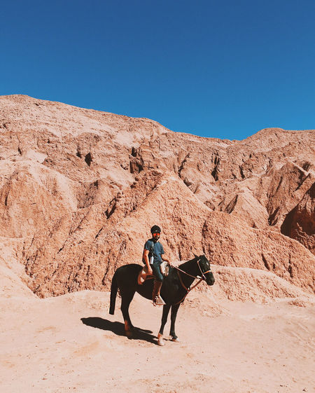 Man Riding Horse Against Rock Formation At Atacama Desert