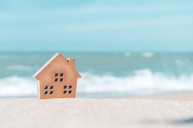 House on beach by sea against sky