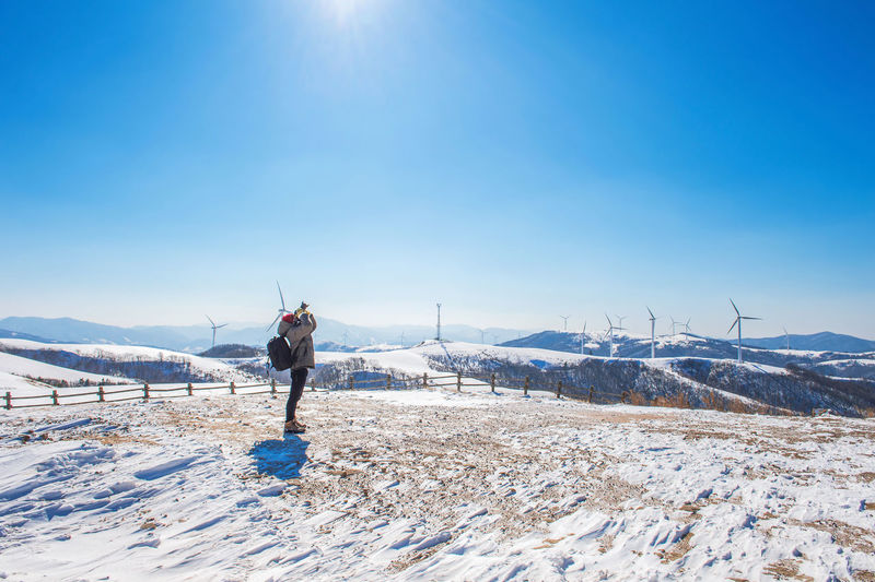 Full length of person photographing through camera while standing on snow covered landscape against blue sky