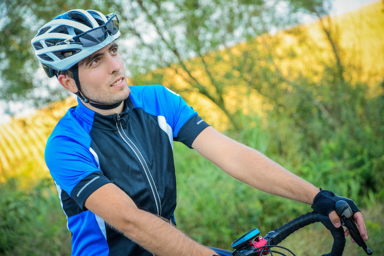 Thoughtful Young Man Wearing Cycling Helmet While Looking Away