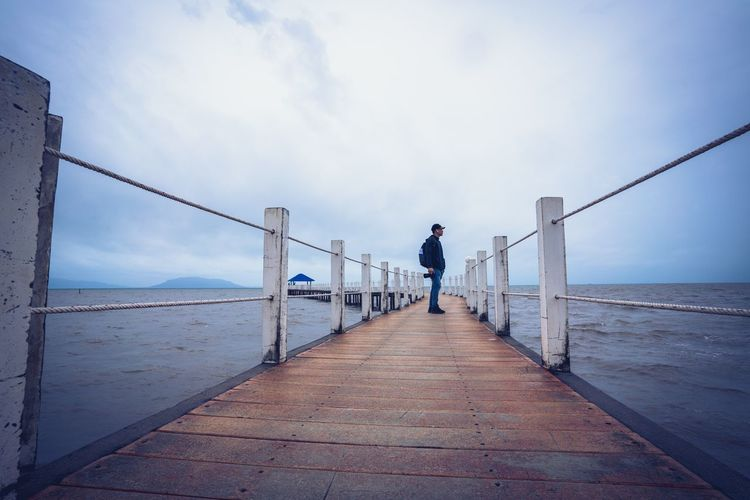 Man standing on pier at sea
