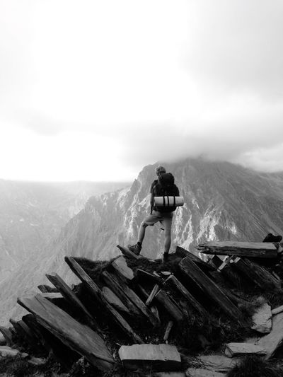 Rear View Of Hiker Standing On Mountain Against Cloudy Sky