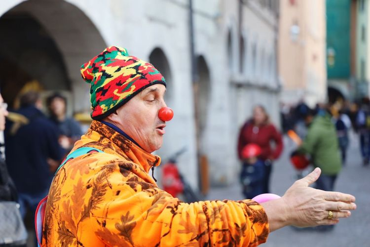 Man in clown costume performing on road in city