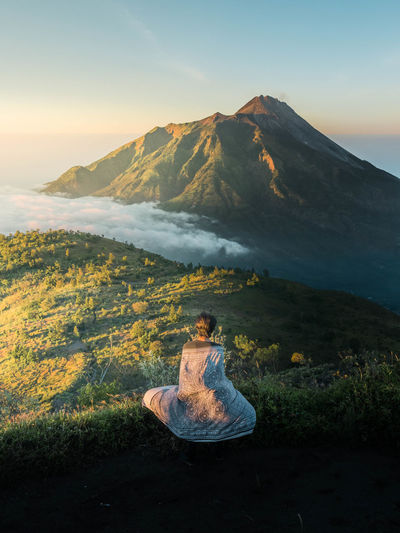 Woman sitting on land against sky