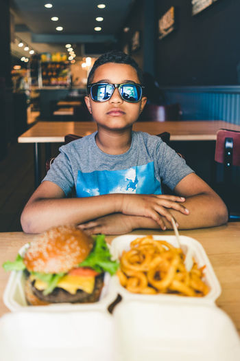 Portrait of boy with sunglasses eating fast food at restaurant