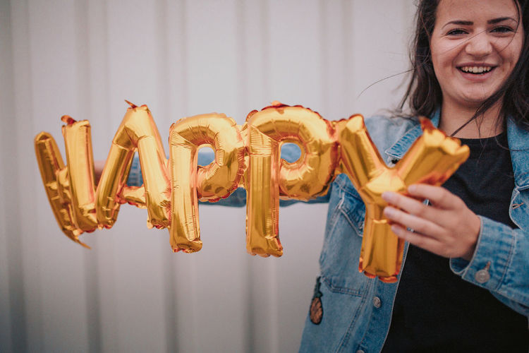 Young laughing woman is holding golden happy ballon in the air EyeEm Selects EyeEm Gallery EyeEmNewHere Fun Happiness Happy People Party Time Signs Balloon Balloons Emotion Happiness Happy New Year Holding Lifestyles One Person Party Real People Smiling Teenager Young Women