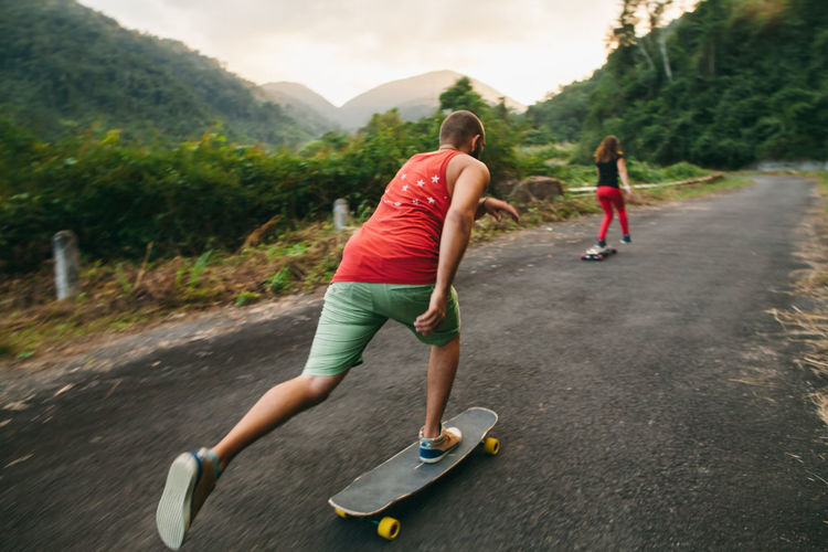 Rear view of people skateboarding on road against mountains