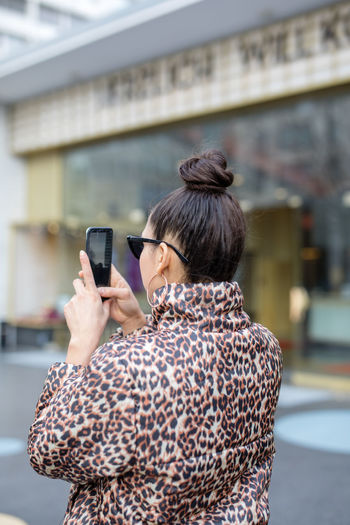 Rear View One Person Smart Phone Adult Wireless Technology Technology Communication Mobile Phone Real People Women Hairstyle Portable Information Device Holding Architecture Telephone Casual Clothing Connection Using Phone Photography Themes Focus On Foreground Outdoors