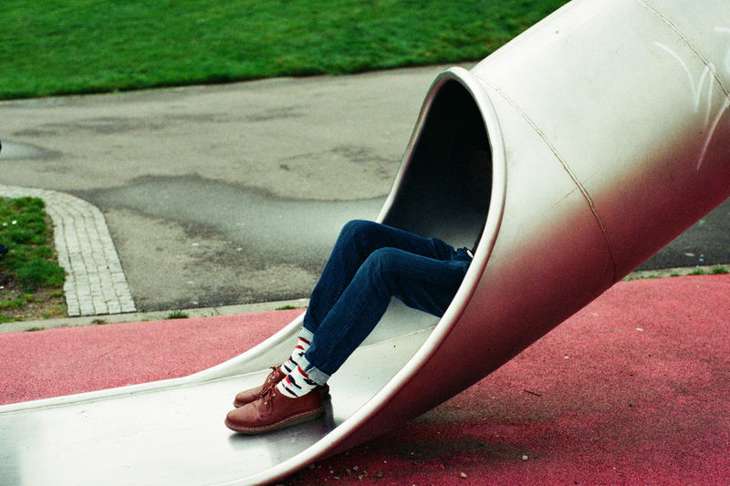 Low section of boy playing on slide in playground