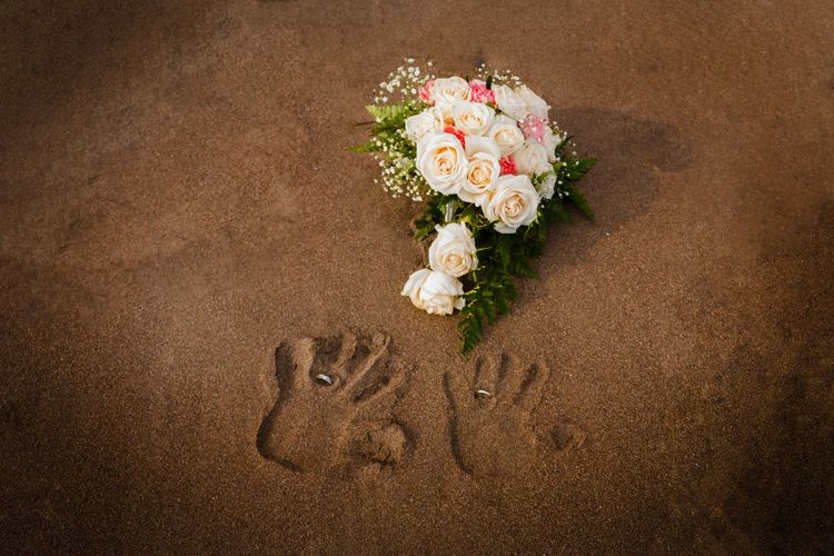 High angle view of rose bouquet and handprints at beach