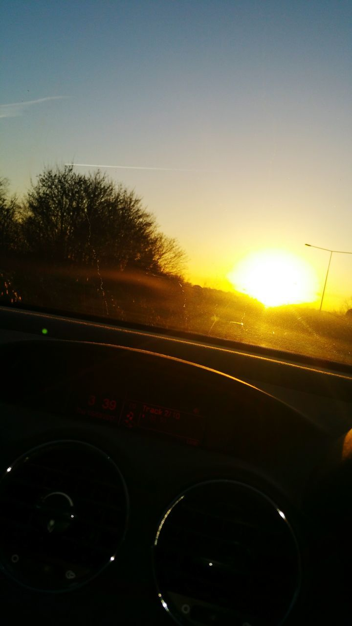 car, sun, lens flare, vehicle interior, sunset, land vehicle, car interior, transportation, no people, mode of transport, windshield, sunlight, tree, close-up, car point of view, sky, nature, speedometer, day, outdoors
