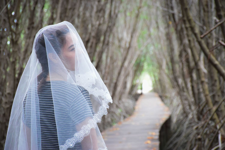 Young Woman Wearing Veil While Standing Amidst Trees