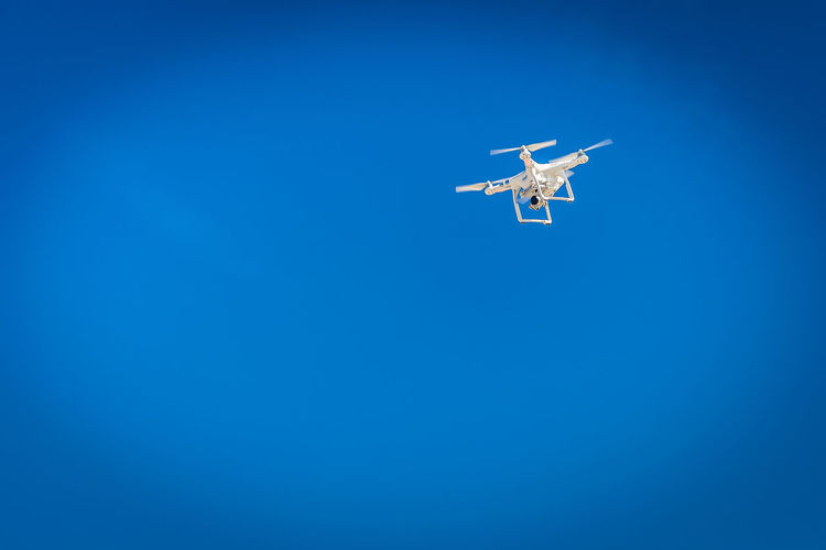 Low Angle View Of Drone Flying Against Clear Blue Sky During Sunny Day