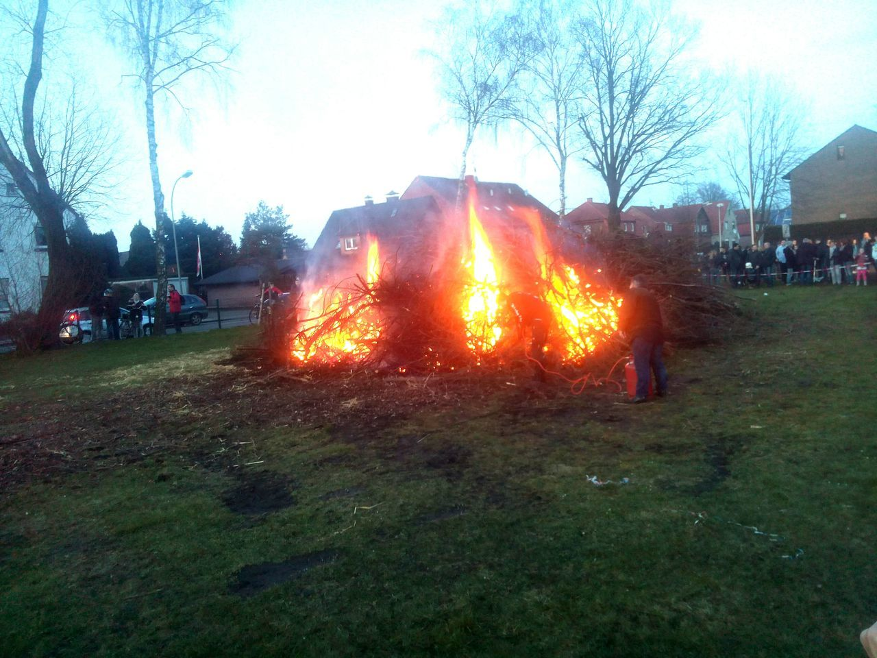 burning, tree, flame, real people, men, incidental people, leisure activity, field, grass, outdoors, large group of people, heat - temperature, women, bonfire, built structure, sky, nature, day, bare tree, building exterior, architecture, people