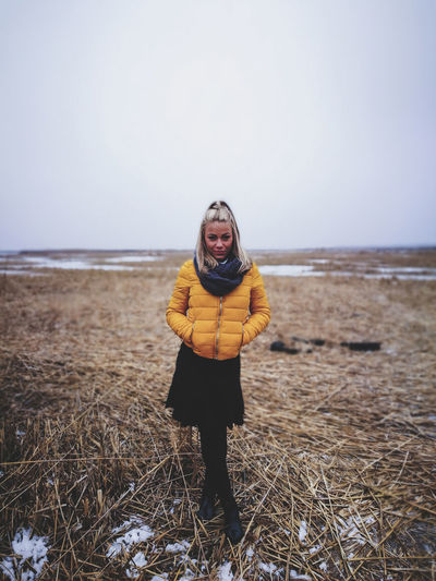 Full length of woman with hands in pockets standing on hay against sky during winter