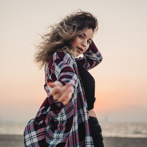 Portrait of young woman standing against sea during sunset