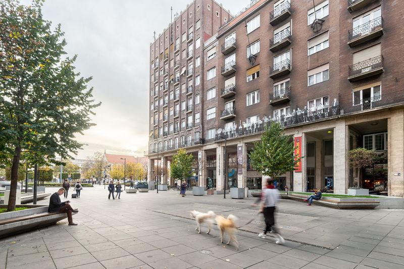 People walking on sidewalk by buildings in city