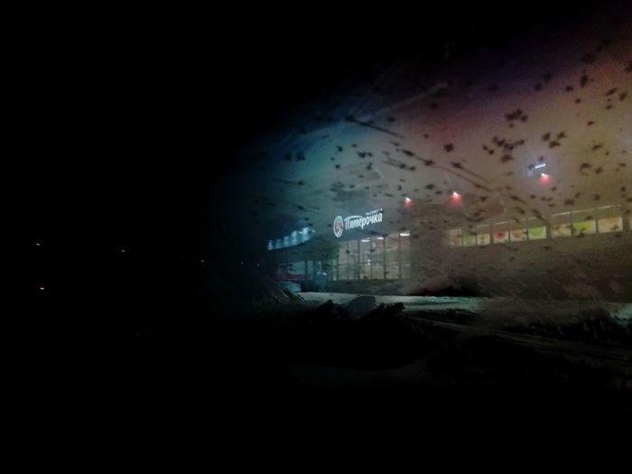 Illuminated city seen through window at night