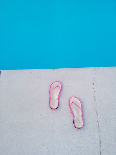 High angle view of flip-flop by swimming pool