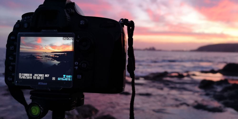 Close-up of camera on beach against sky during sunset